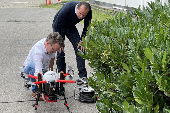 Prof. Dr. Guenter Huhle und Jörg Brinkmeyer (l.) beladen die Drohne mit einem Defibrillator.